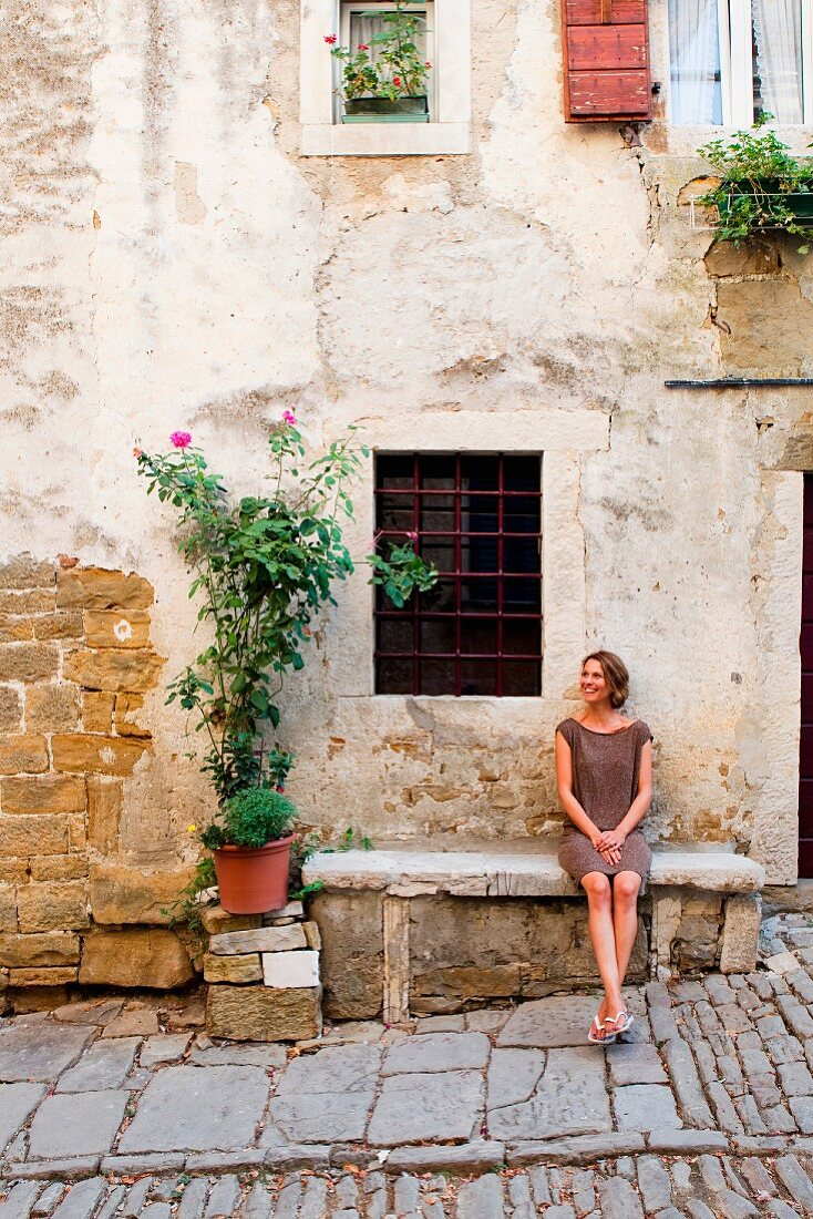 A woman sitting on a stone bench outside a house in Istria, Croatia