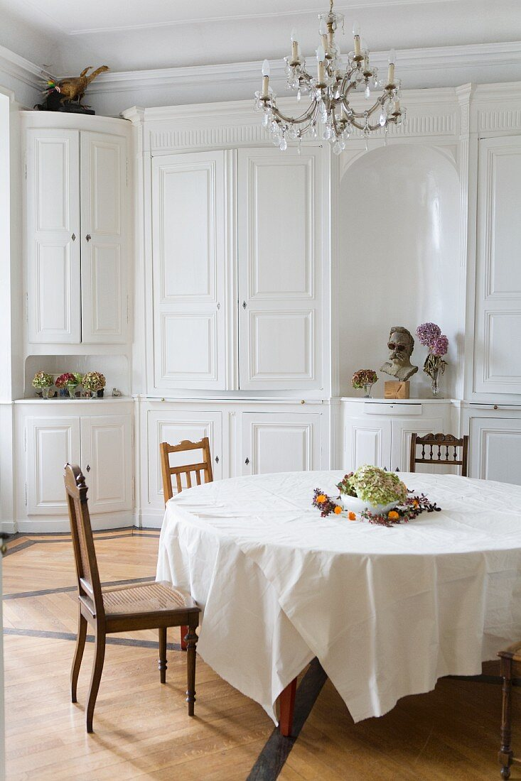 White dining room with a round table in a former monastery