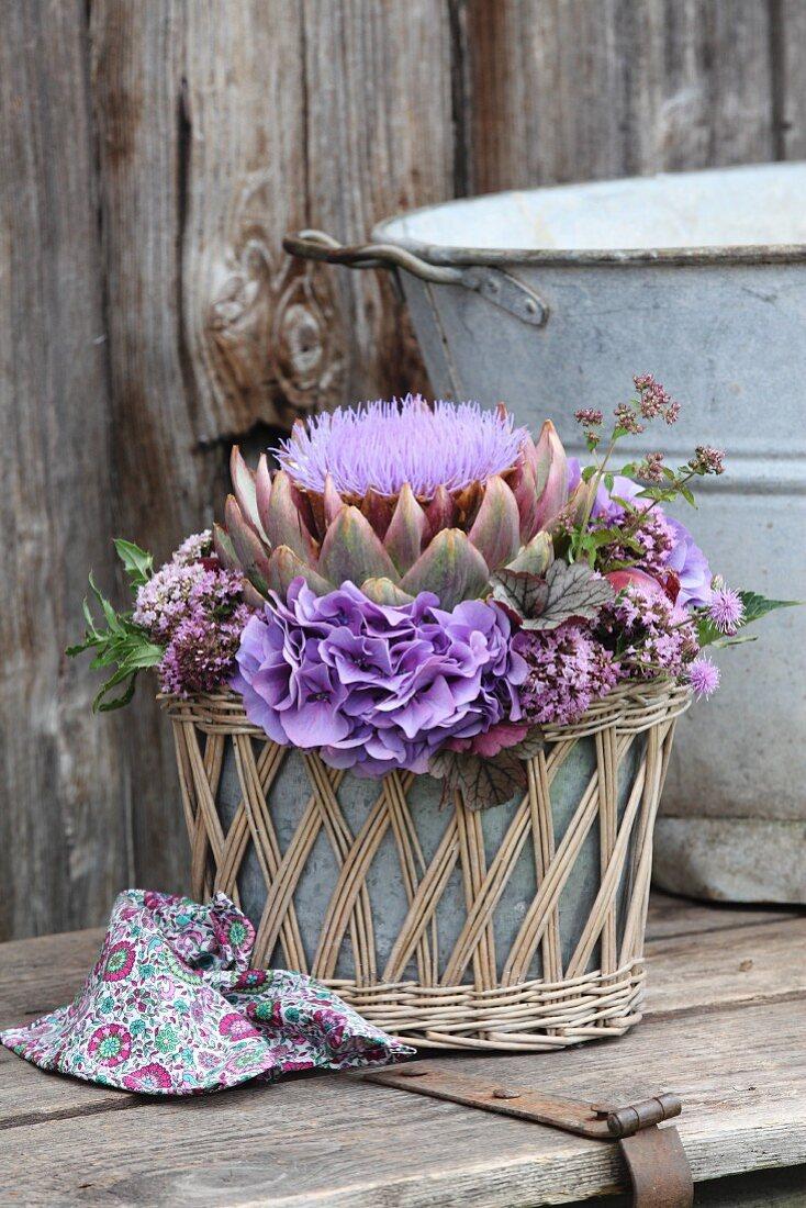 Arrangement of artichoke flower, hydrangeas and flowering marjoram in wicker basket