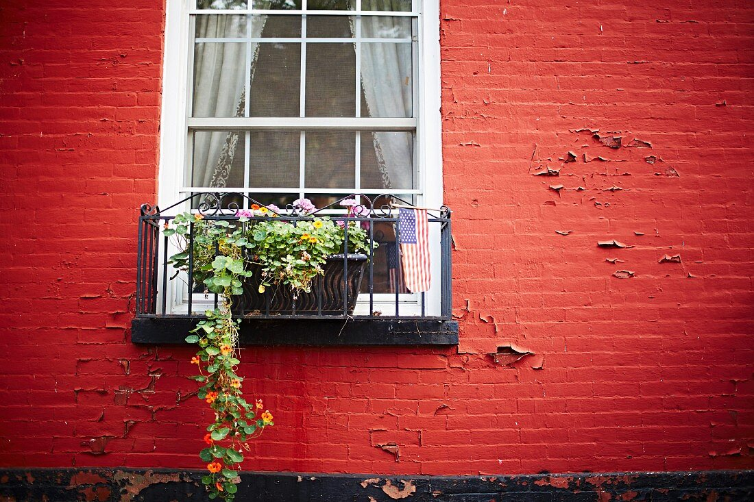 Red house facade with windows, window box & flag of the United States of America
