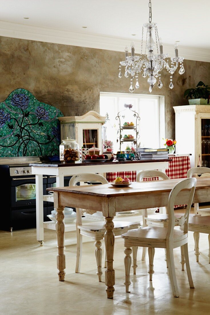 Country-house-style kitchen with shabby chic table and chairs below chandelier