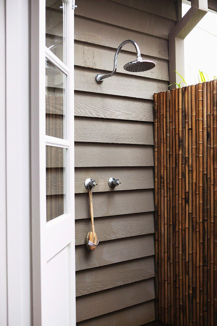 Outdoor shower on wooden wall of house; partially visible bamboo screen