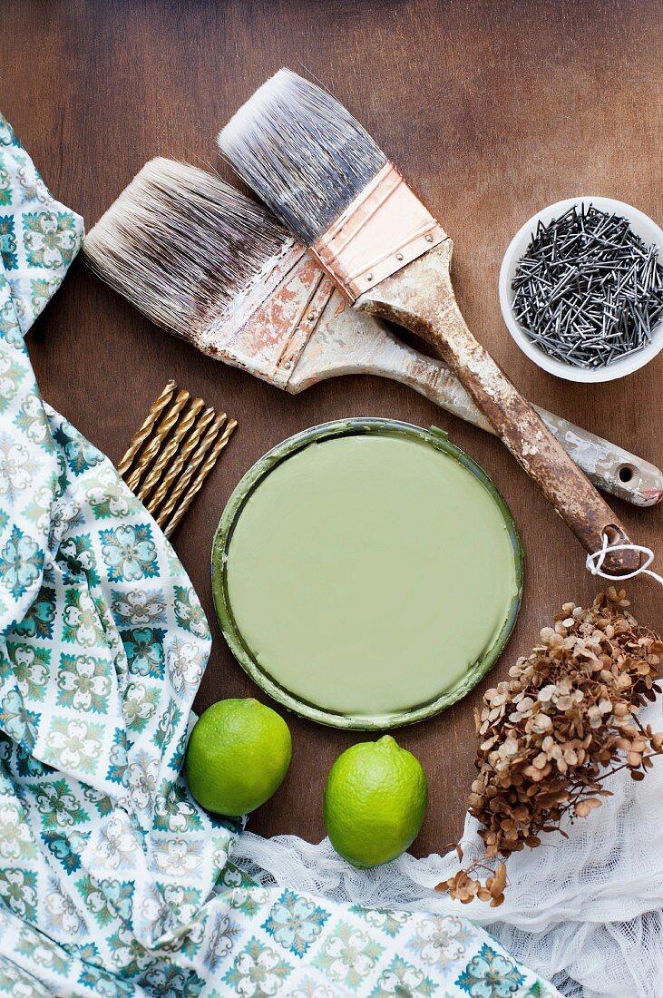 Still-life of paintbrushes, nails, screws, paint pot lid & decorative fabrics