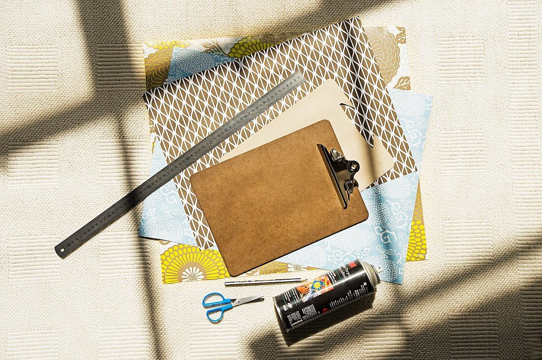 Sheets of variously patterned paper, clipboards, metal ruler, scissors and spray can