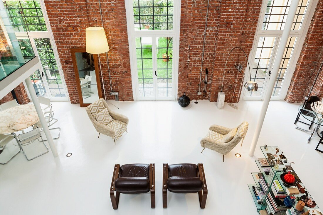 View from gallery into loft apartment with widely spaced armchairs and designer standard lamps against brick wall with floor-to-ceiling windows
