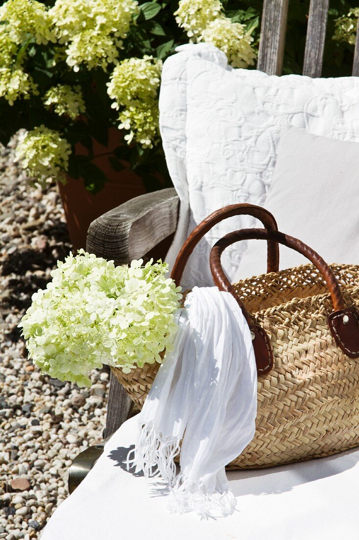 White cushions and raffia bag on deckchair in front of country house