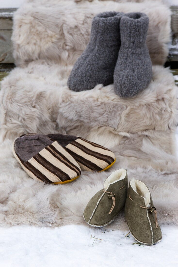 Various slippers (knitted, lambskin and fur-lined mules) on fur blanket in snow