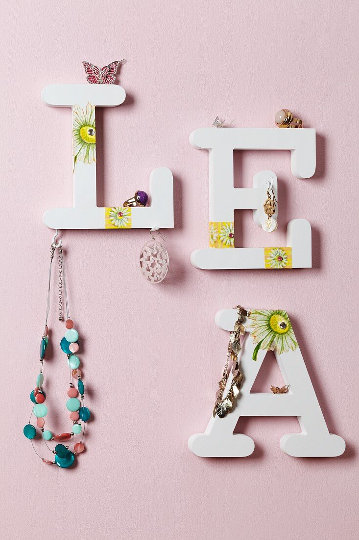 Jewellery hanging from decorative letters on wall