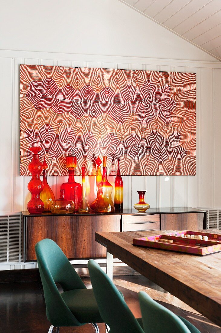 Indigenous Australian artwork above collection of artistic glass bottles (Blenko) on 50s sideboard and classic Executive chairs (Saarinen) around dining table in foreground