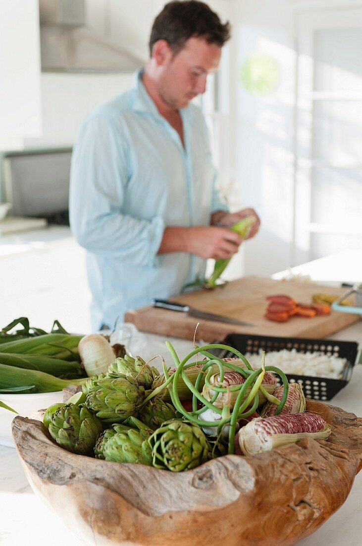 Artichokes and corn-on-the-cob in root wood bowl; man preparing meal on large chopping board in background