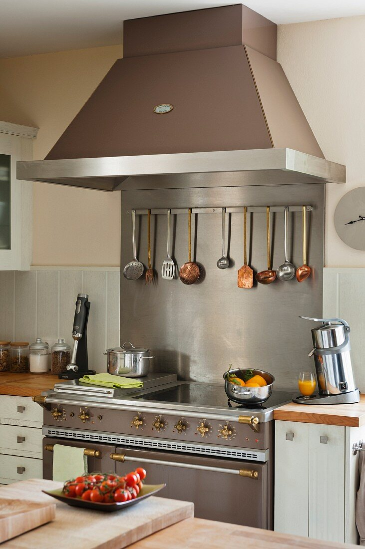 Modern electric cooker with retro elements and cooking utensils hanging from bar below extractor hood