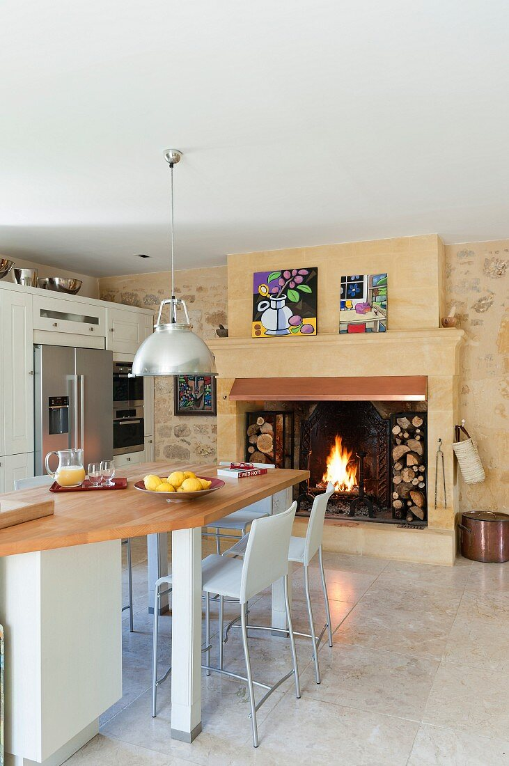 Open fireplace with integrated firewood storage in kitchen-dining room with industrial-style pendant lamps above counter-height table