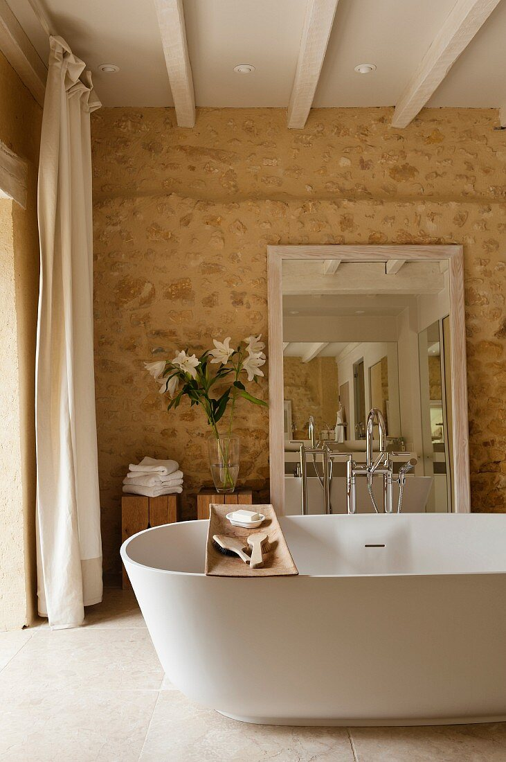 Free-standing bathtub with wooden shelf and mirror leaning against stone wall in ensuite bathroom