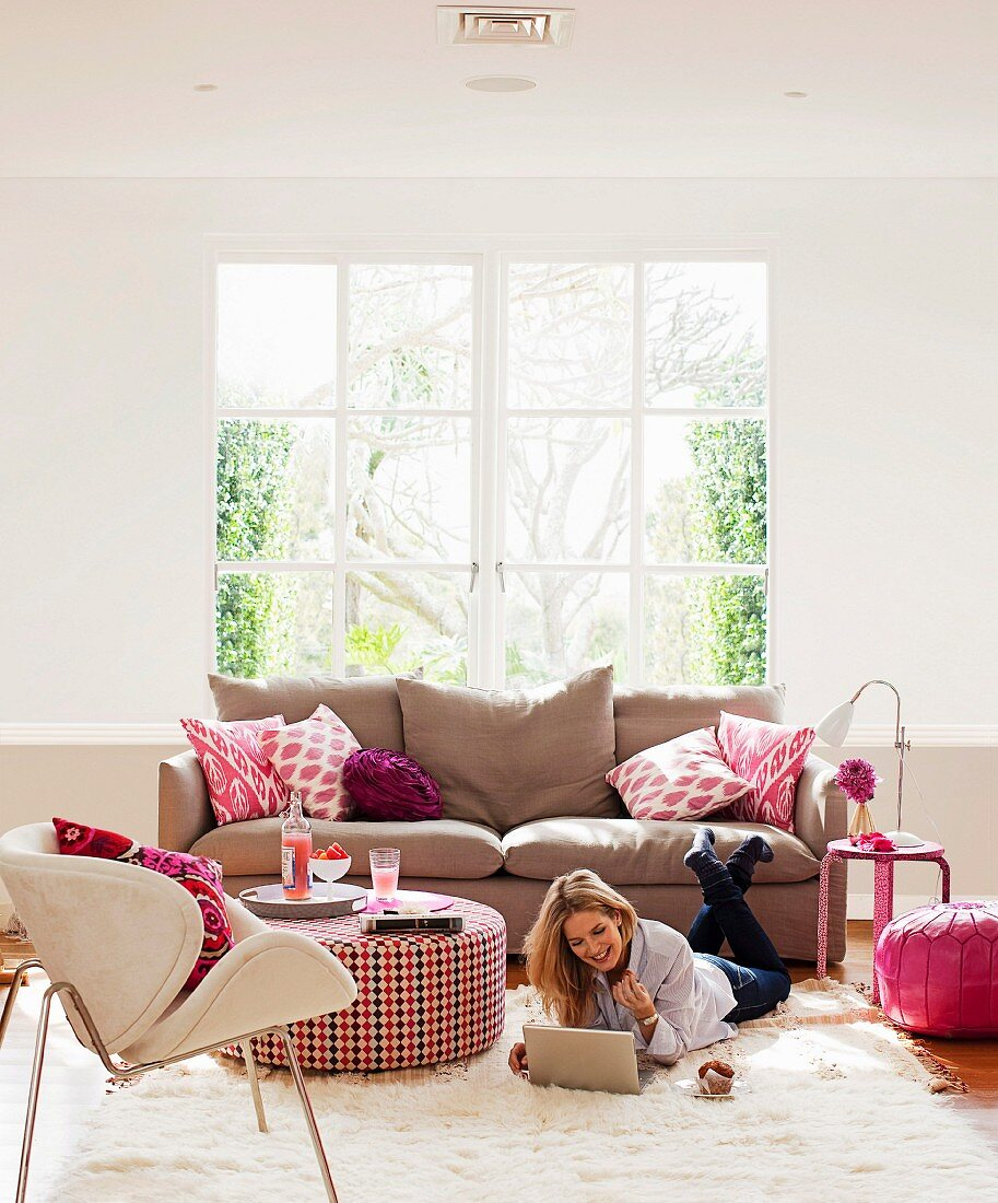 Pink colour accents in living room; sofa cushions, flowers, ottoman and pouffe