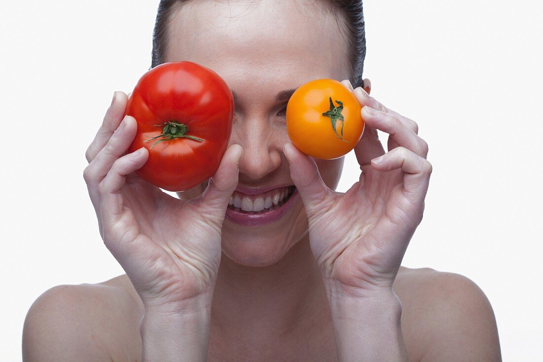 Lachende Frau mit roter und gelber Tomate