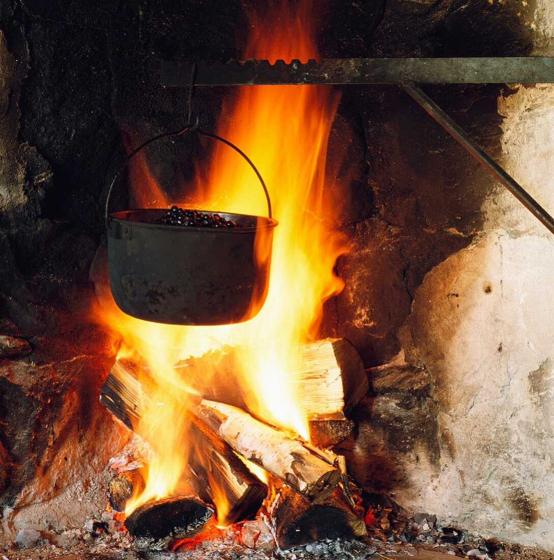 Bilberries cooking in pot over open fire