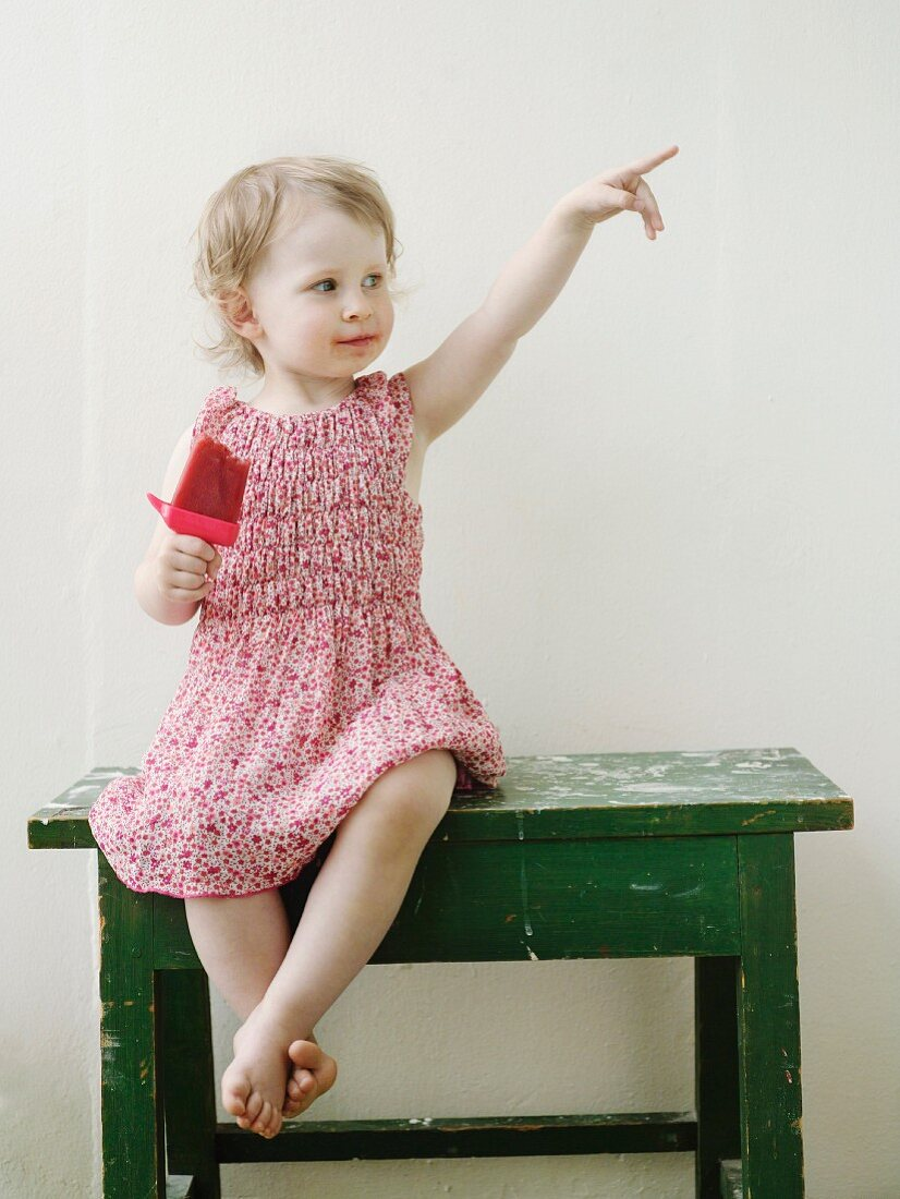 Little girl eating ice lolly sitting on small table