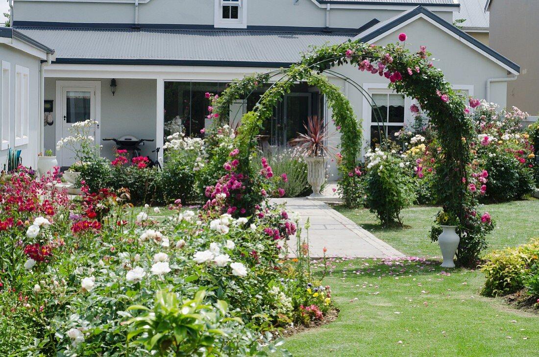 Prachtvoll blühender Garten mit Blumenrabatten und Rosenbögen