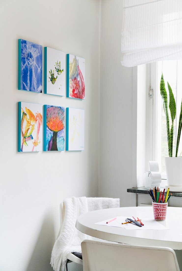 Paintings on wall near kitchen table
