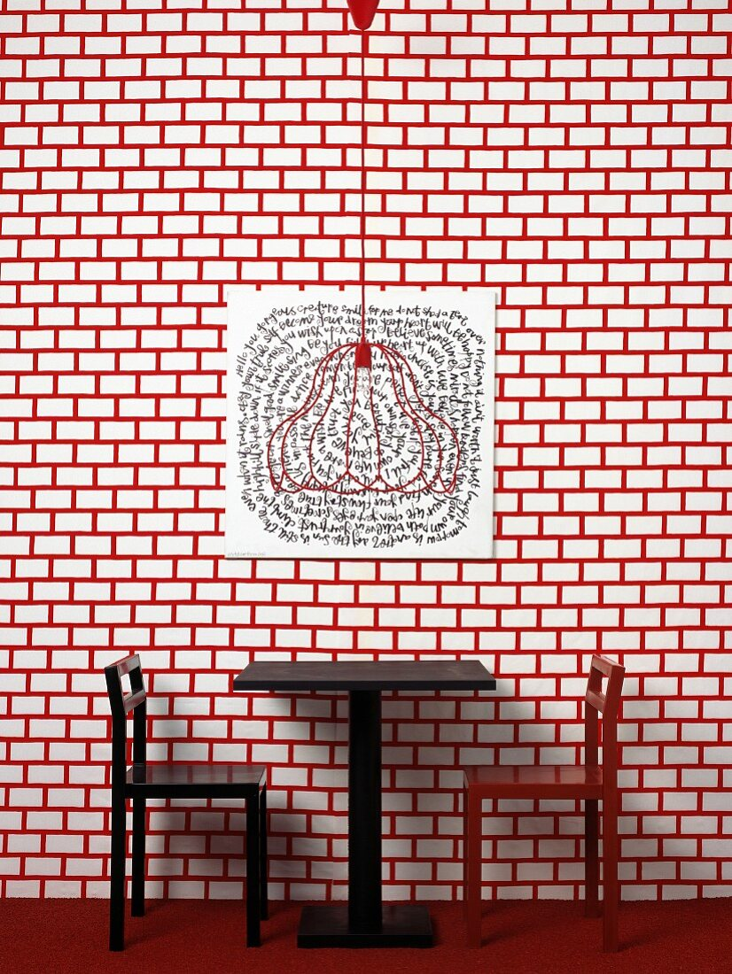 Table and chairs against red and white patterned wall
