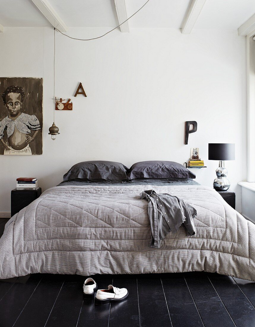 Large quilt on double bed in bedroom with black wooden floor