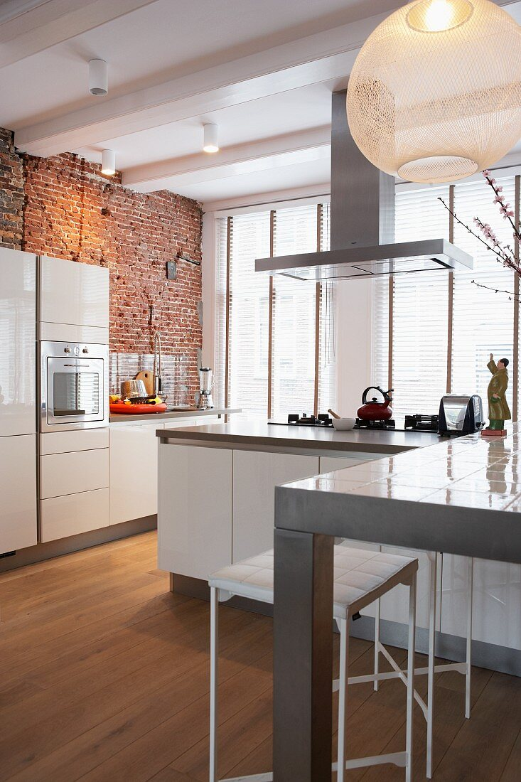 Modern kitchen with white units and rustic, brick rear wall in front of large windows