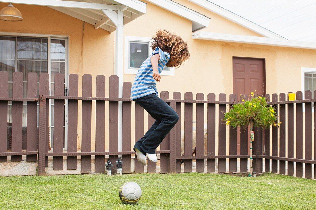 Boy jumping over football