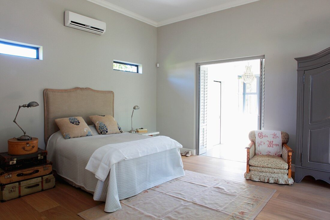 Double bed with upholstered headboard and armchair next to open terrace door in minimalist, air-conditioned bedroom