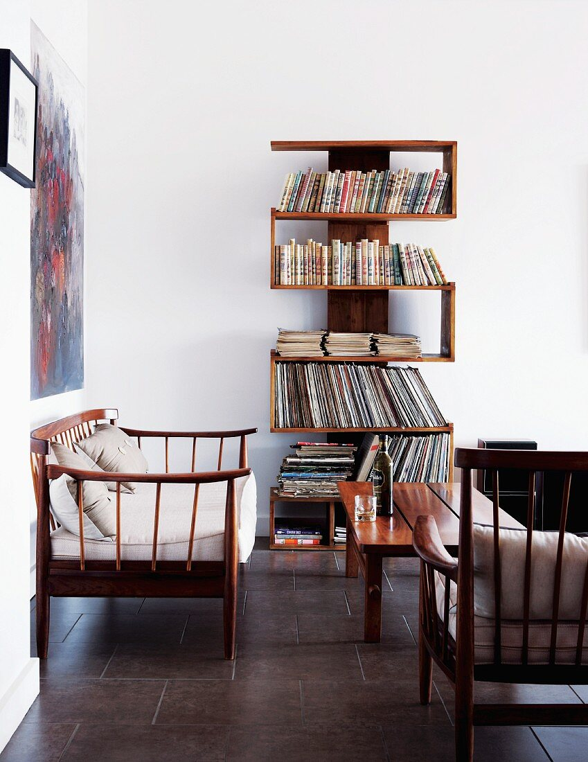 Unusual, winding bookshelves against white wall in simple, bright living room with delicate wooden furniture
