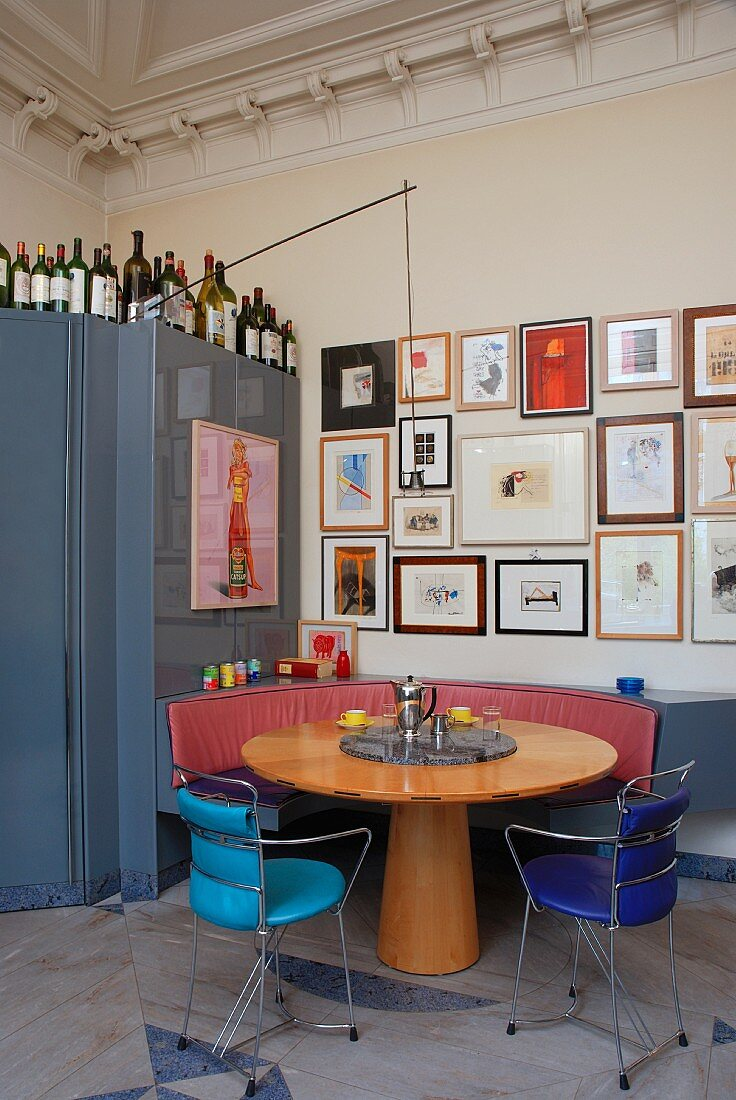Round, Biedermeier-style wooden table and delicate metal chairs in front of collection of pictures on wall and blue metal cupboard with bottles on top