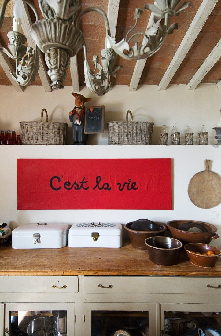 White enamel bread bins and ceramic pots on rustic kitchen worksurface; aphorism written on red paper