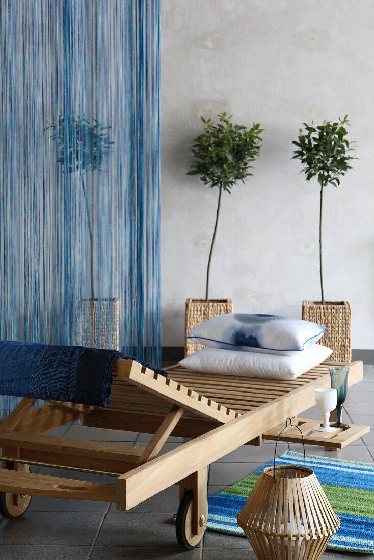 Liegestuhl aus Holz vor kleinen Bäumen im Topf mit Rattan Übertopf
