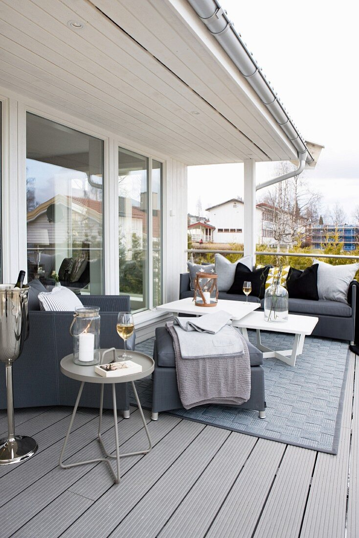 Grey sofa set, side tables and rug on balcony adjoining glass facade of Scandinavian wooden house
