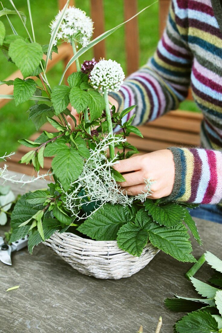 Woman's hands arranging garlic flowers in small basket