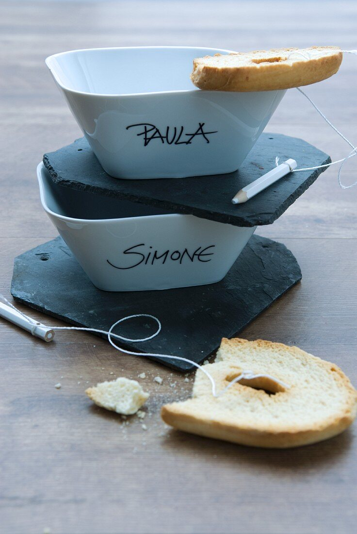 Names written on bowls, small slate boards and toasted bagels tied to crayons with string