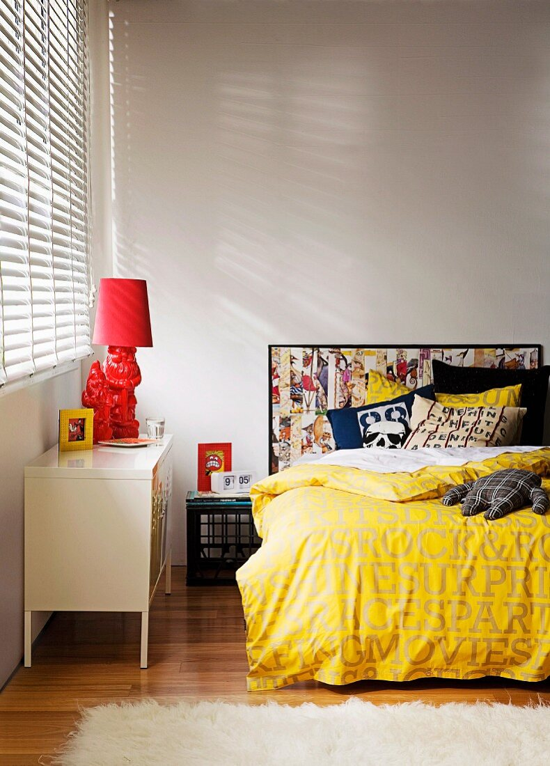 Bed in teenager's bedroom with headboard hand-crafted from frames comic pages, scatter cushions hand-sewn from old shirts & bedside lamp made from painted garden gnomes