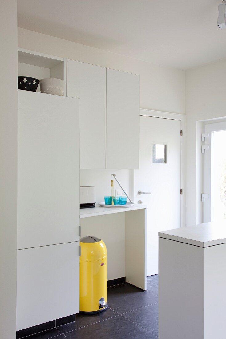 Schlichte weiße Einbauküche mit knallgelbem Retro Mülleimer