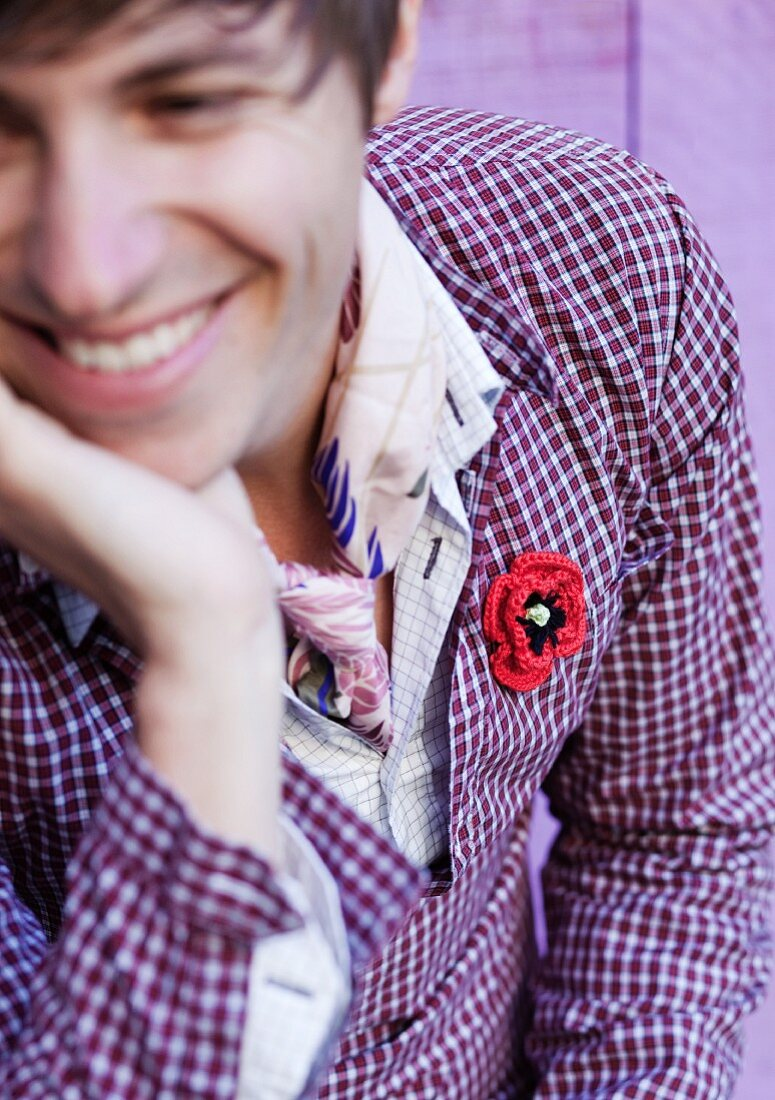 Smiling young man wearing crocheted flower badge on purple checked shirt