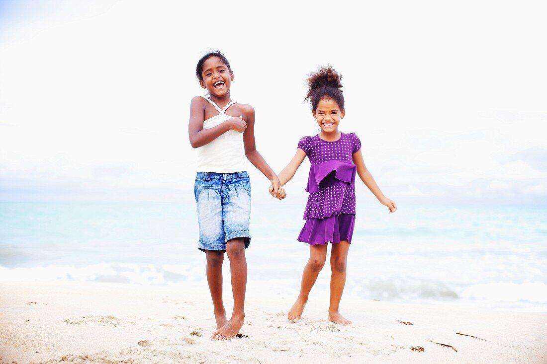 Two dark-skinned girls standing on beach hand in hand