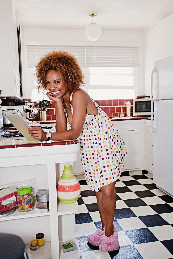 Dark-skinned woman in nightdress holding tablet computer in kitchen