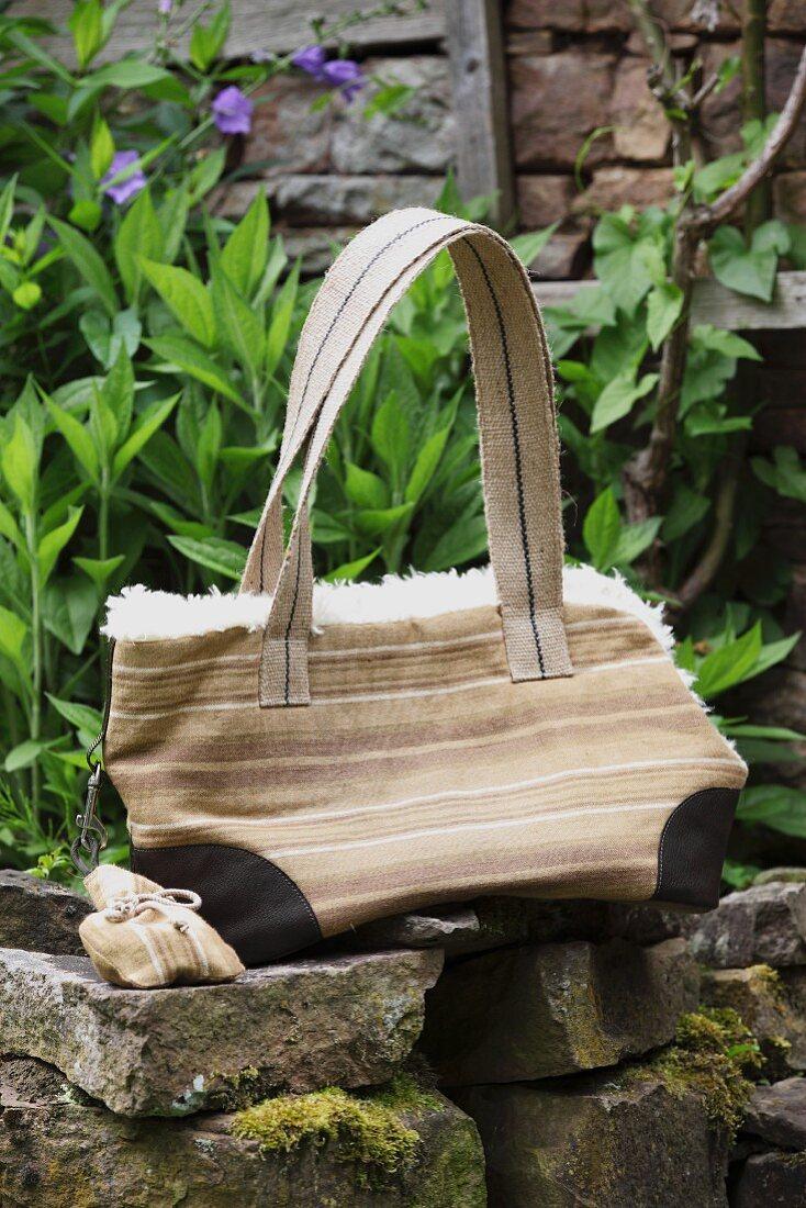 Hand-sewn handbag with fleecy lining on stone wall in garden