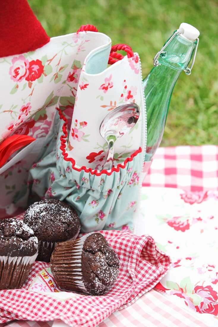 Chocolate muffins on checked tea towel and partially visible cloth picnic bag with floral pattern