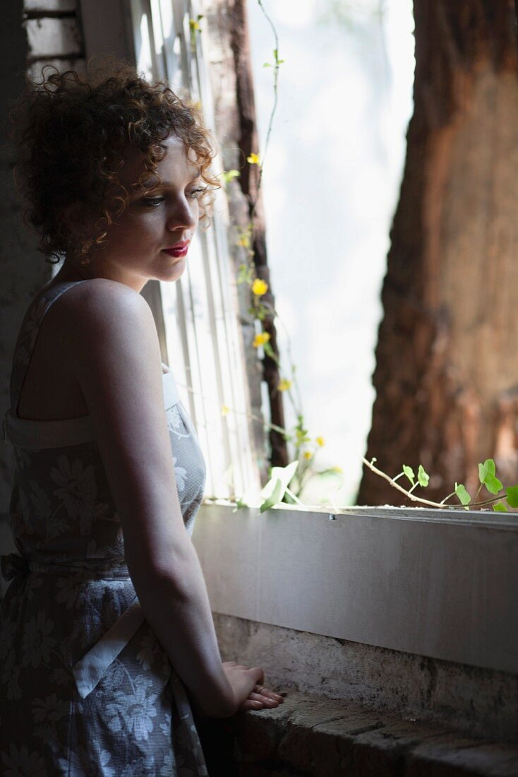 Young woman standing by window daydreaming