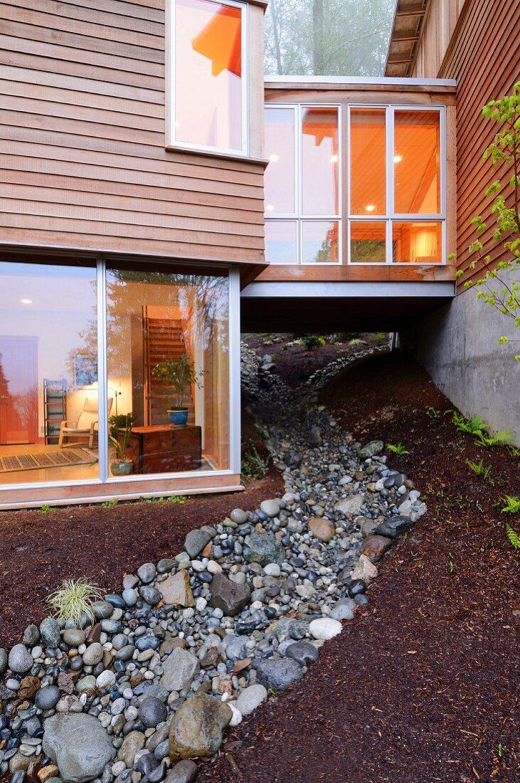Kleiner Verbindungsbau über dem Kiesbett zwischen den Trakten eines modernen Holzhauses am Hang