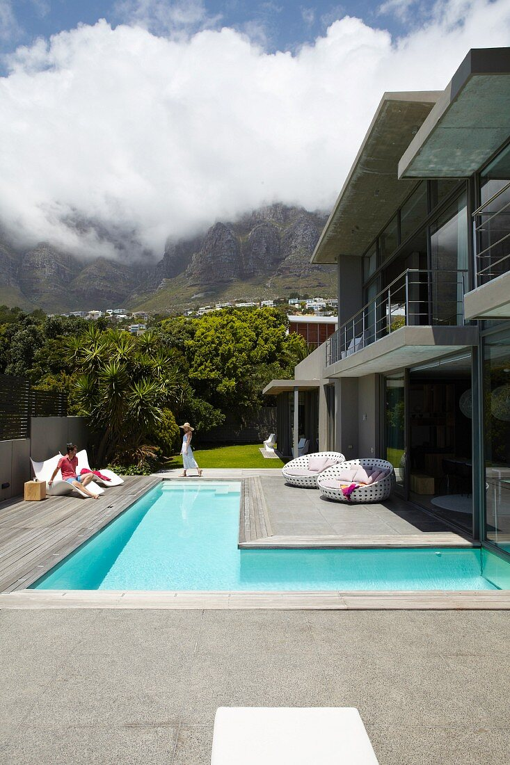 Luxury house with L-shaped floor, terrace and garden below white clouds in blue sky