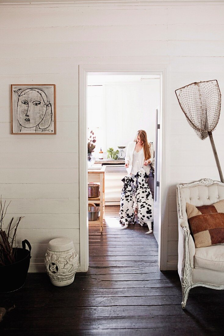 Fishing net and vintage armchair against white wooden wall, dark brown wooden floor and woman with two Dalmatians in kitchen seen through doorway