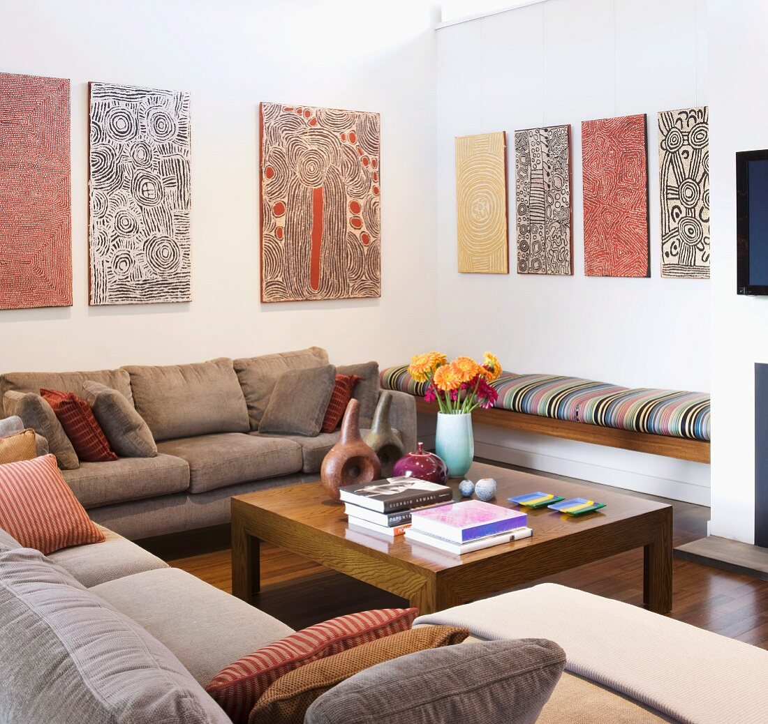 Aboriginal artworks above seating area with comfortable sofas and simple, exotic-wood coffee table