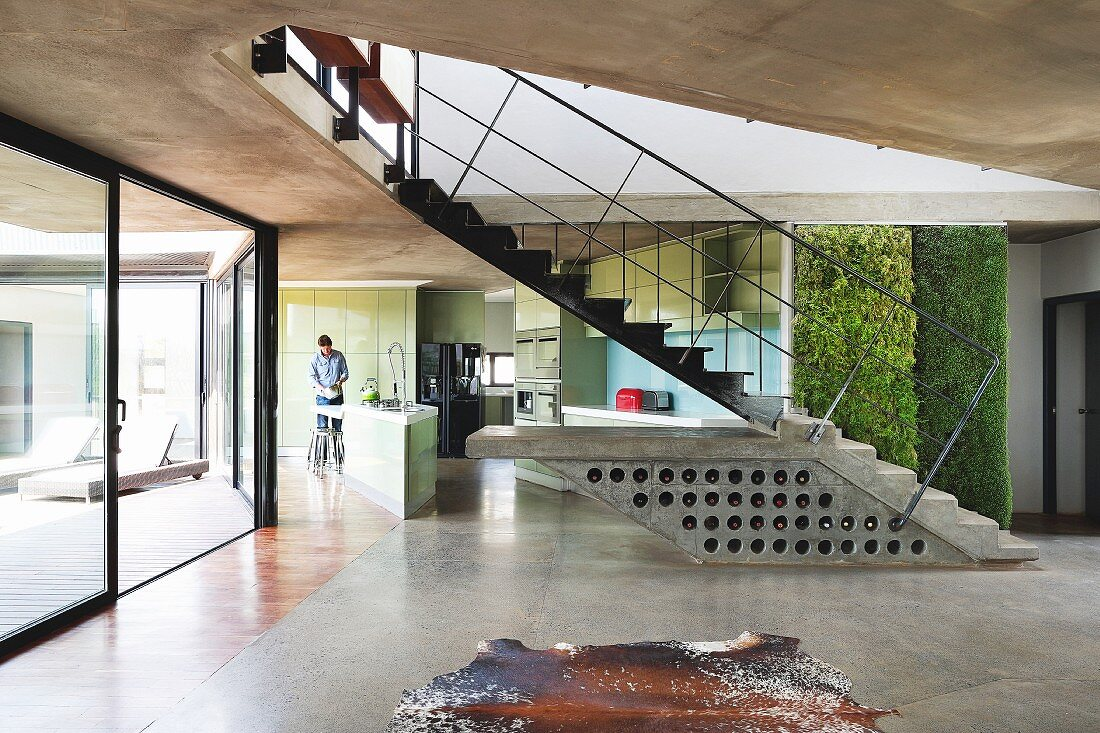 Purist house with exposed concrete ceiling and glass wall with view of courtyard; wine rack in concrete plinth of free-standing staircase