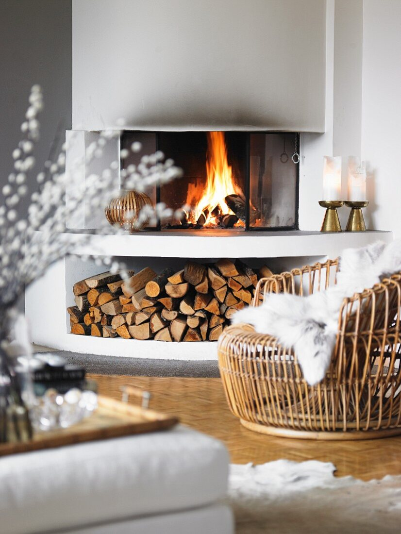 Cosy basketwork armchair with white fur blanket in front of fire in open fireplace with firewood store below