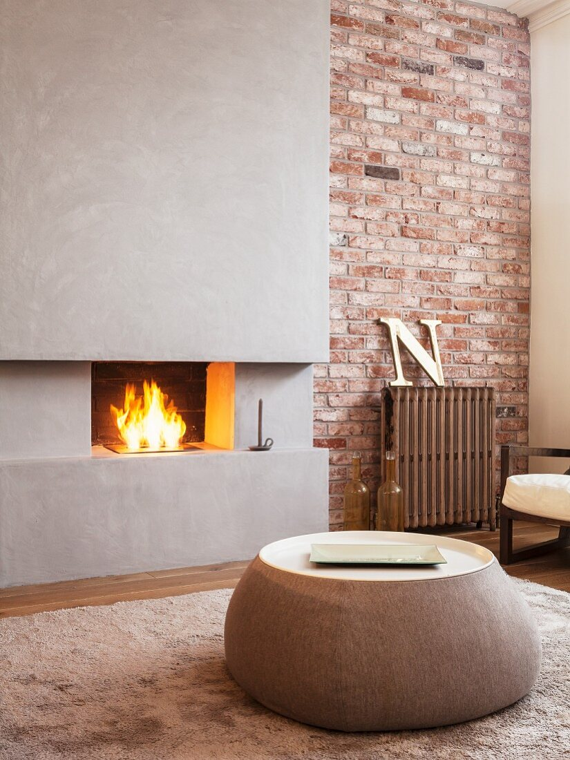Round coffee table in front of open fireplace in concrete chimney breast set in brick wall